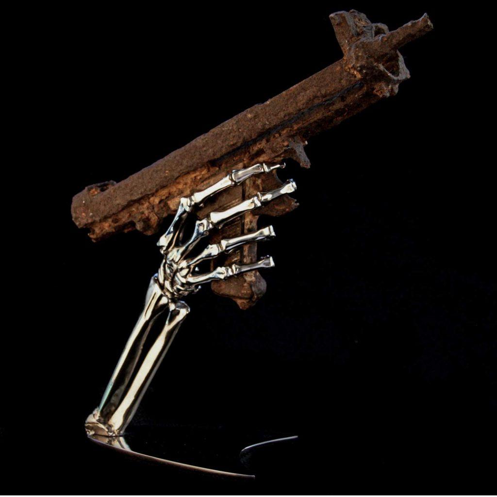 skelton hand gun sculpture with battlefield relic